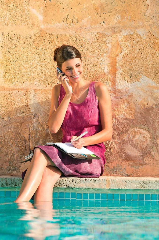 Woman using cellphone with feet in swimming pool : Stock Photo