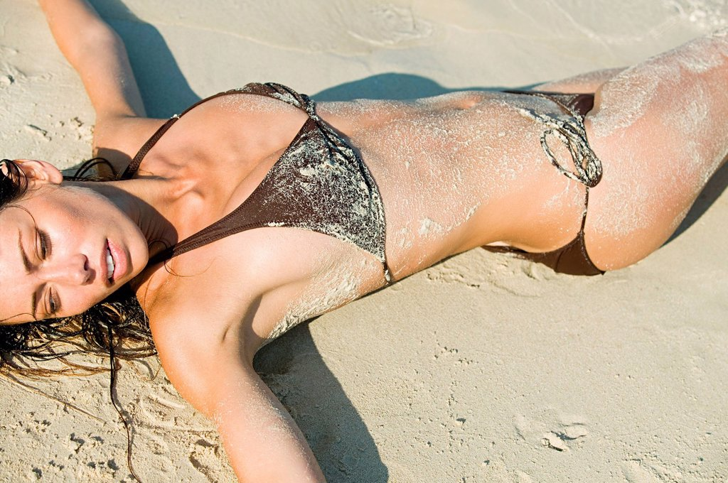 Young sexy woman lying on beach : Stock Photo