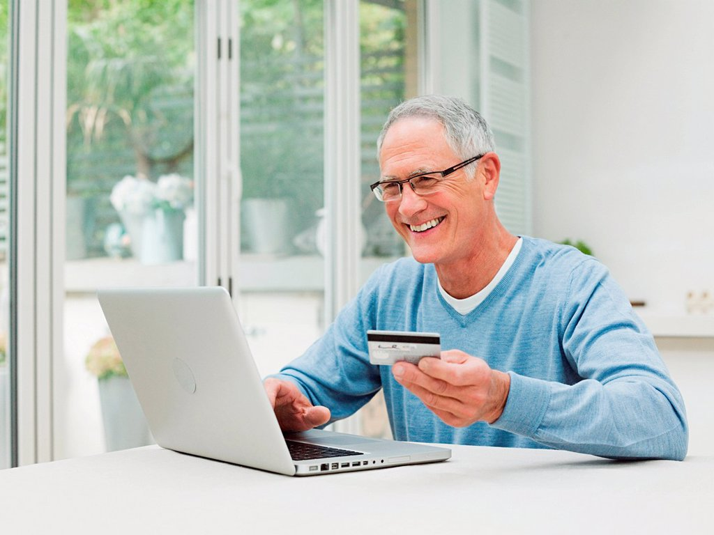 Senior man using laptop with credit card : Stock Photo