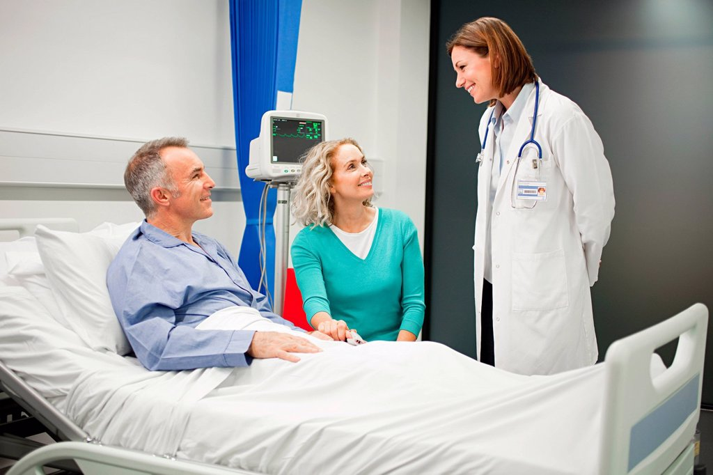 Stock Photo: 1439R-1135243 Wife visiting husband in hospital, talking to doctor