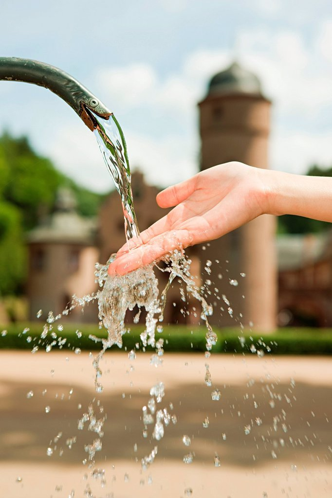 Woman with hand in water fountain, close up : Stock Photo