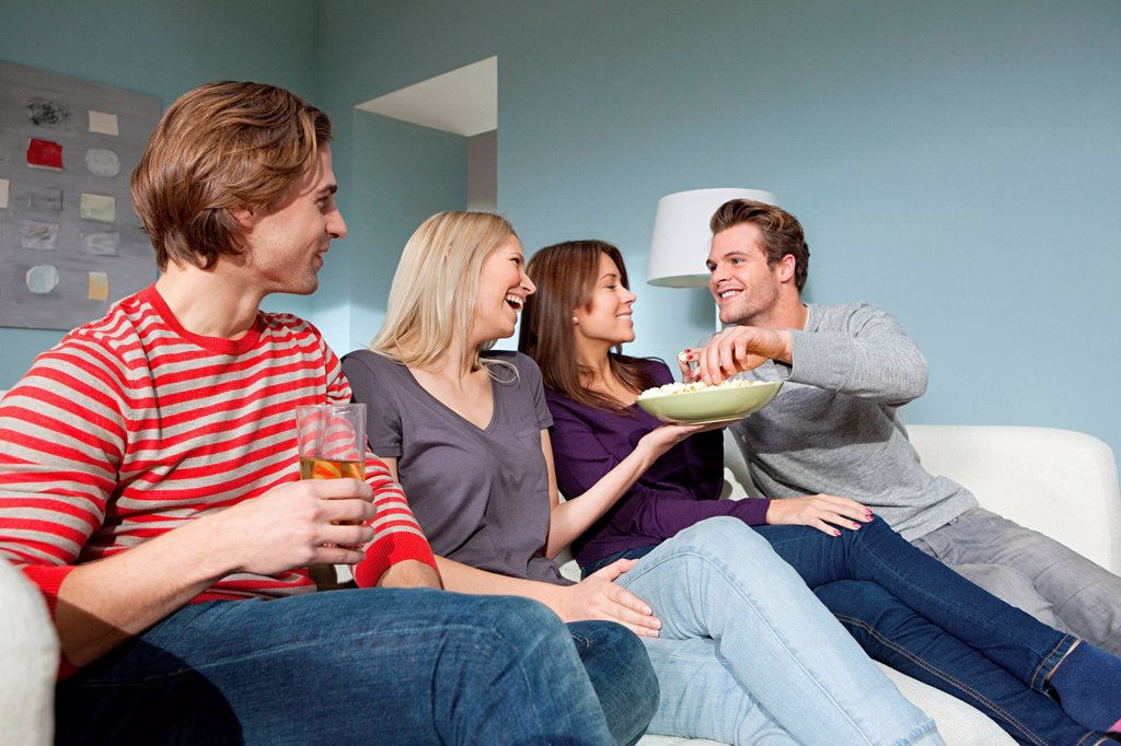 Stock Photo: 1439R-1136087 Two young couples watching television