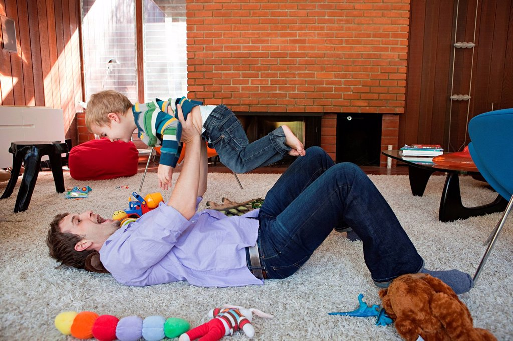 Father lifting son in living room : Stock Photo