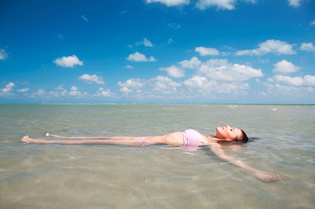 Young woman floating in sea : Stock Photo
