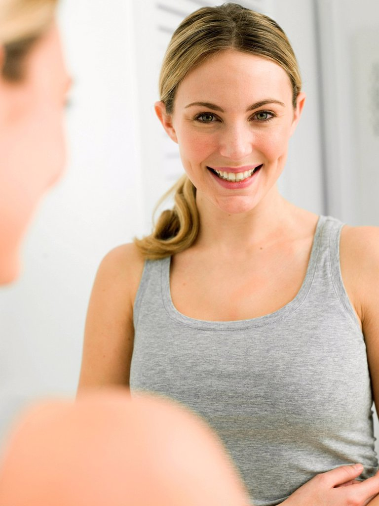 Reflection of young woman in bathroom mirror : Stock Photo