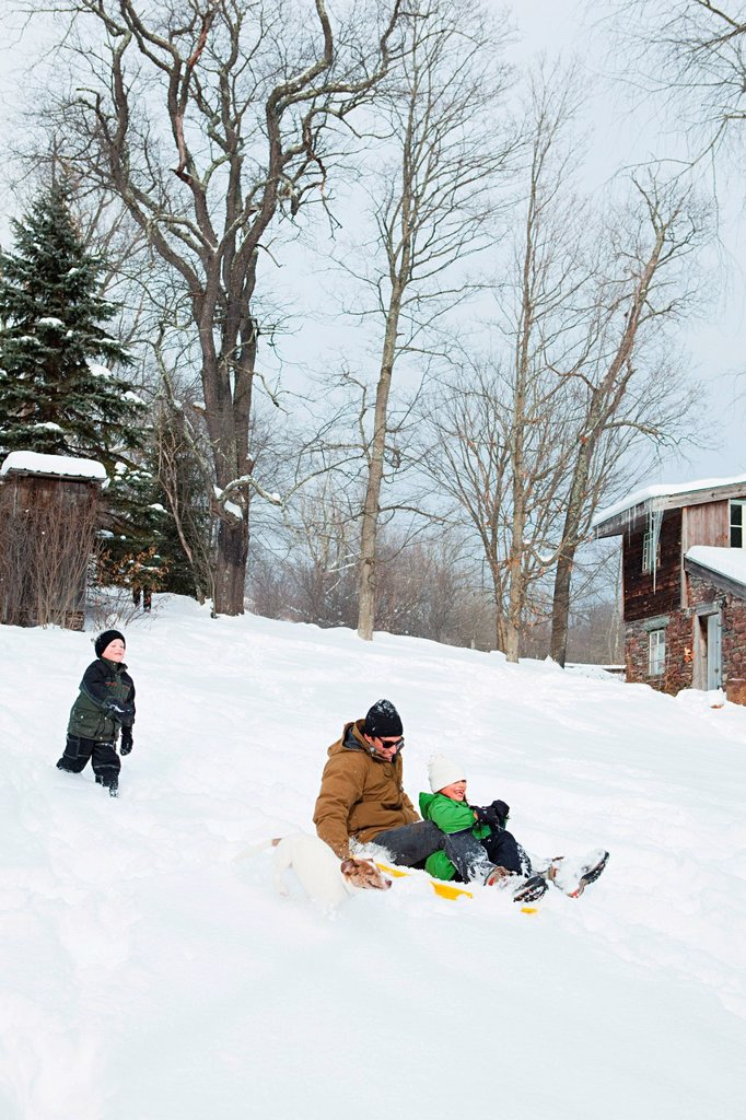 Stock Photo: 1439R-1138721 Family sledging in snow