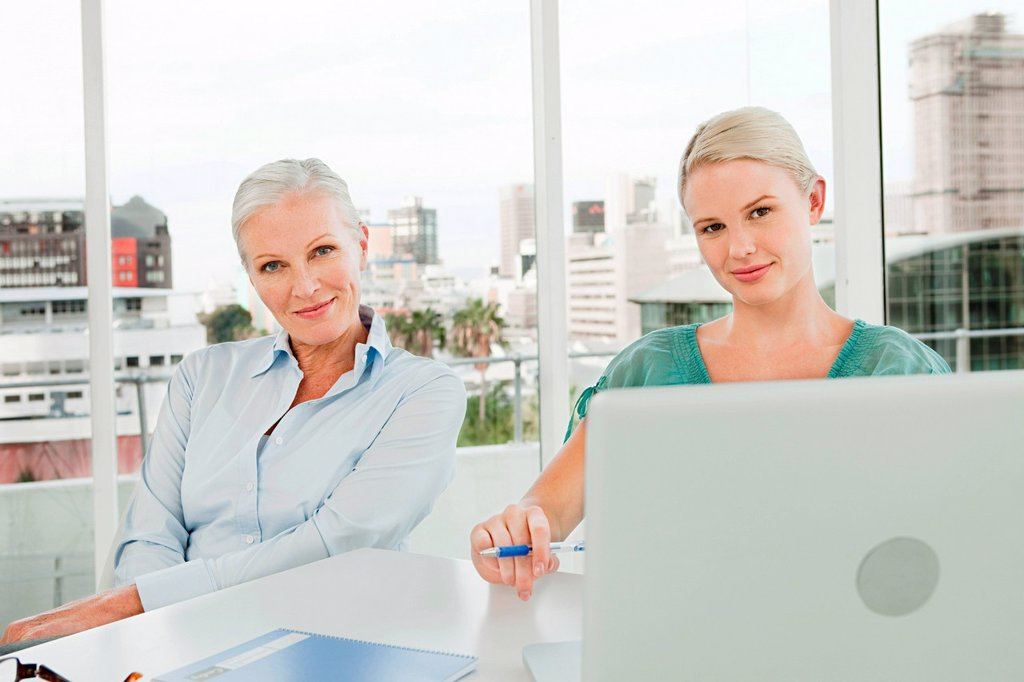 Two businesswomen using laptop in office : Stock Photo
