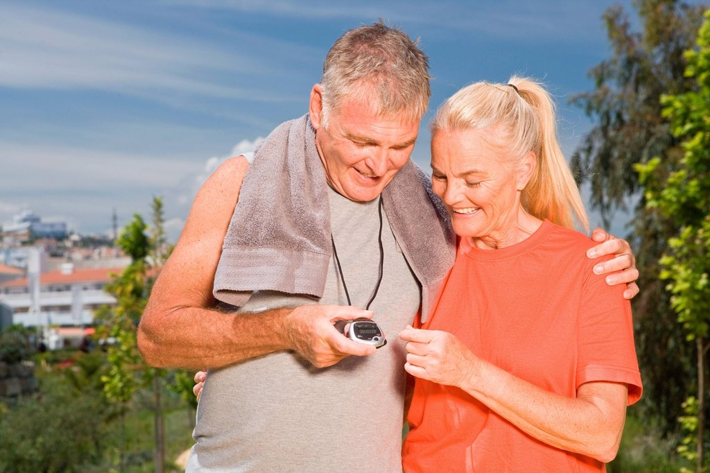 Mature couple looking at stopwatch after workout : Stock Photo