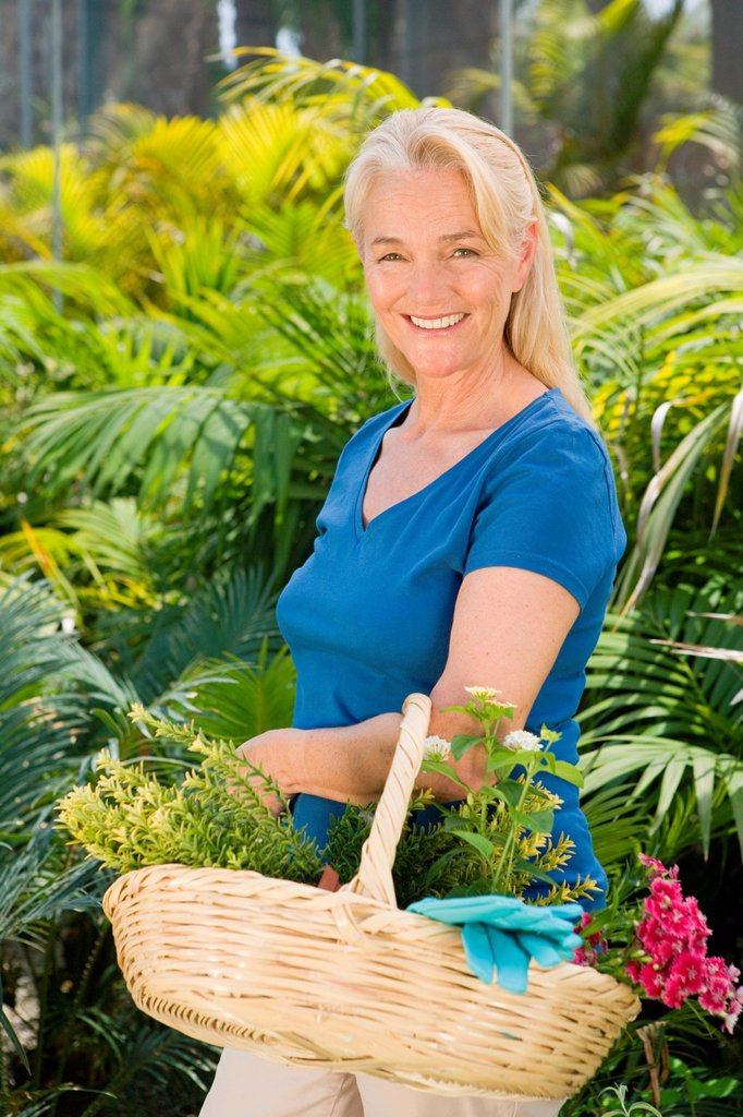 Mature woman amongst plants with basket : Stock Photo