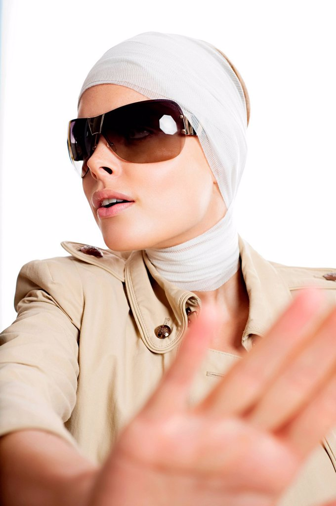 Stock Photo: 1439R-1139430 Young woman in sunglasses and bandages after cosmetic surgery