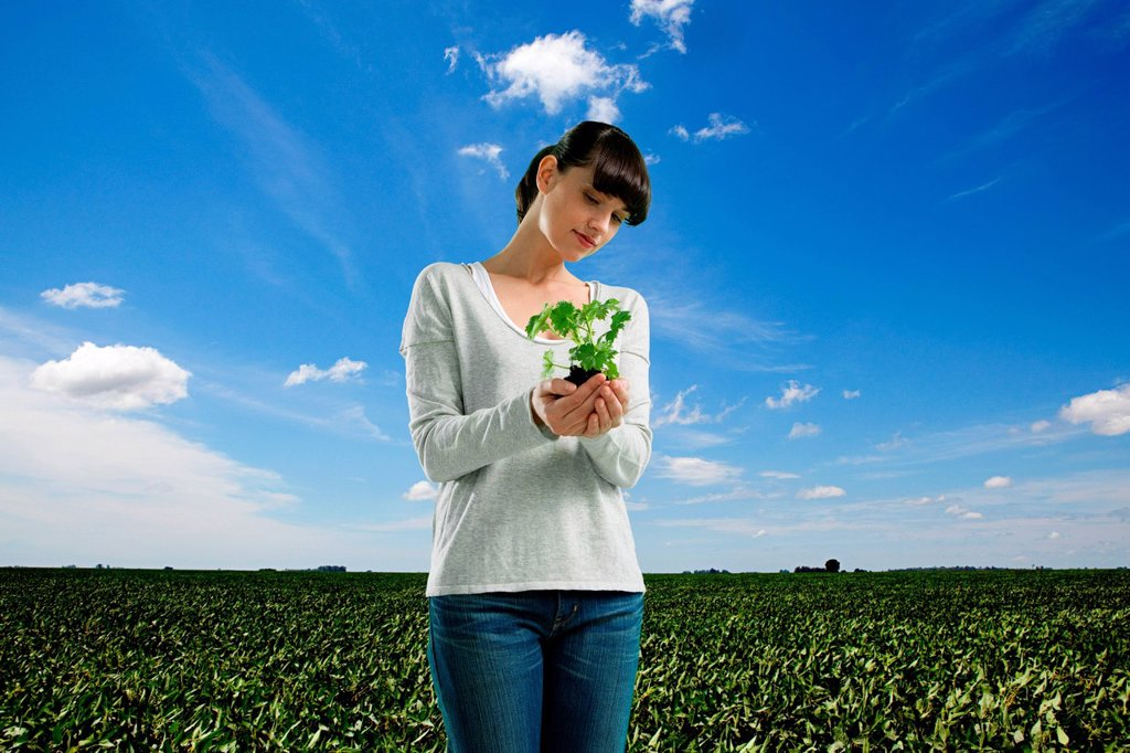 Stock Photo: 1439R-1139560 Young woman holding plant in field