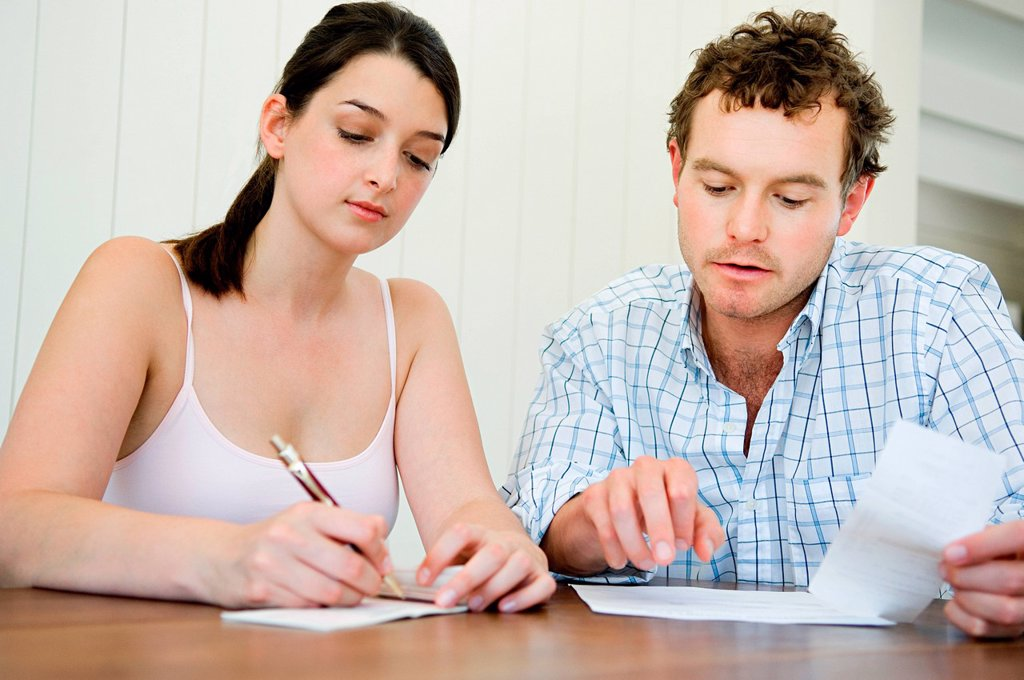 Stock Photo: 1439R-1140247 Couple planning home finances, woman writing cheque