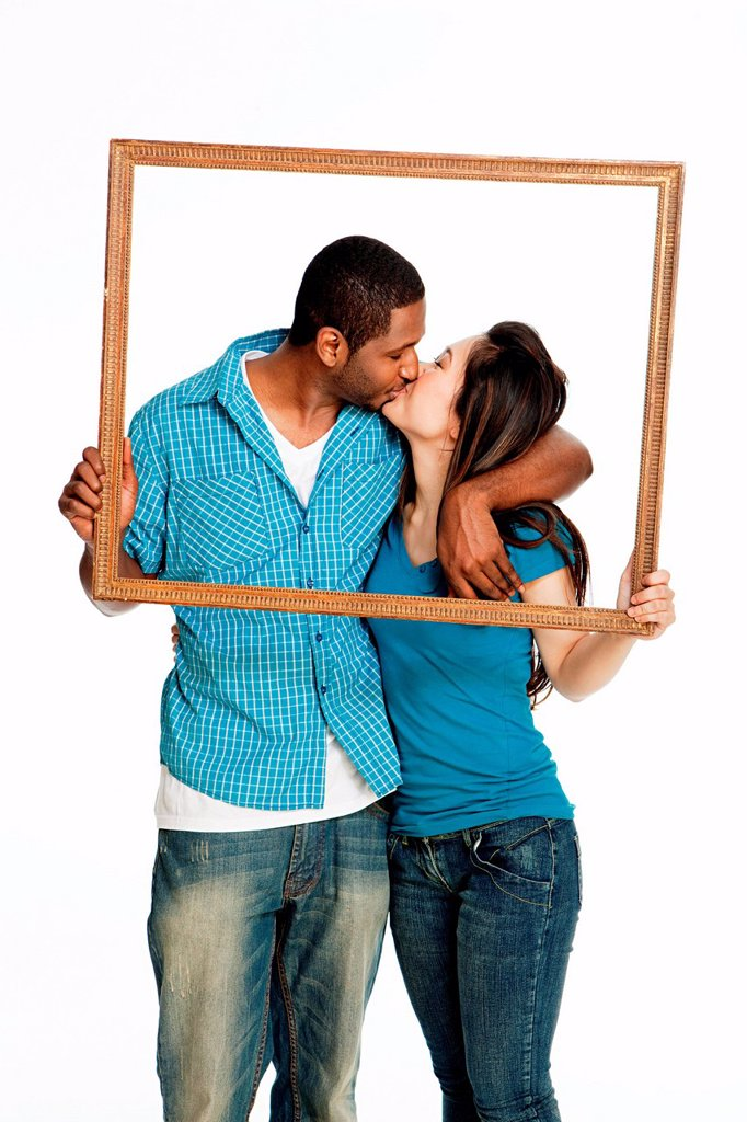 Mixed race couple kissing inside picture frame against white background : Stock Photo