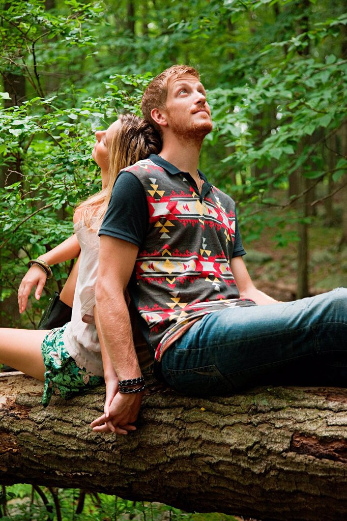 Stock Photo: 1439R-1140522 Couple leaning against each other on log in forest