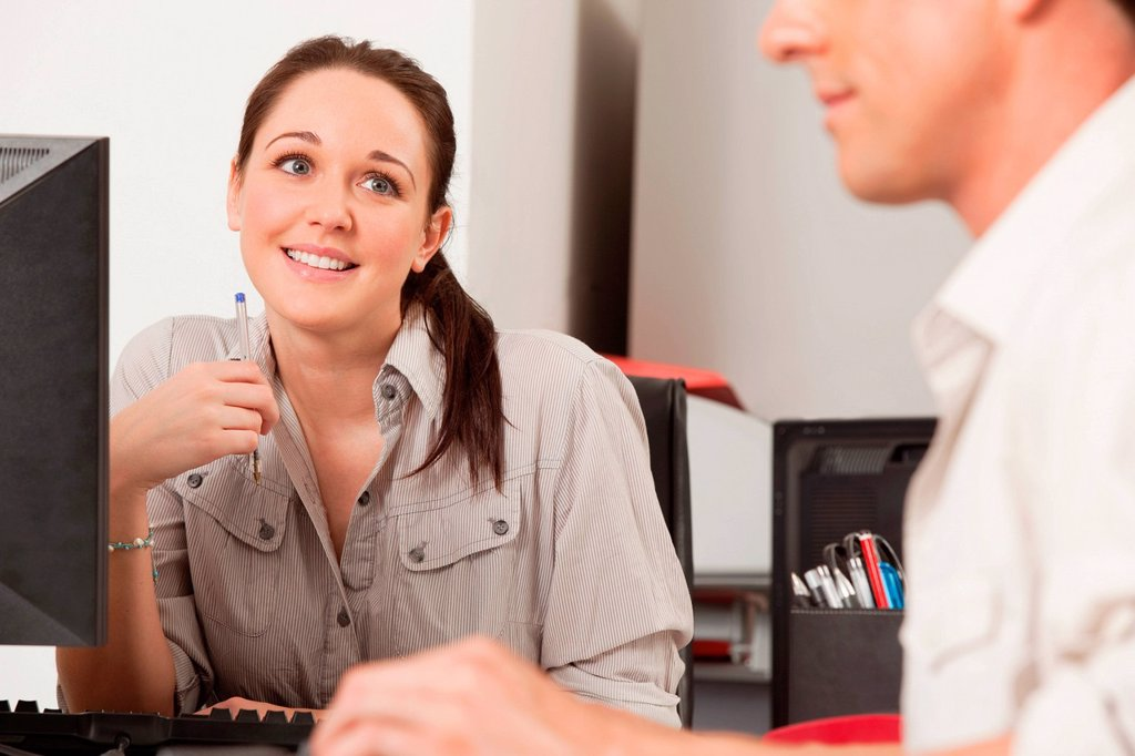 Female employee gazing longingly at her male colleague : Stock Photo
