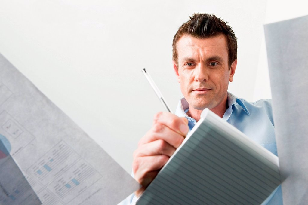 Stock Photo: 1439R-1141098 Business man writing in a notebook