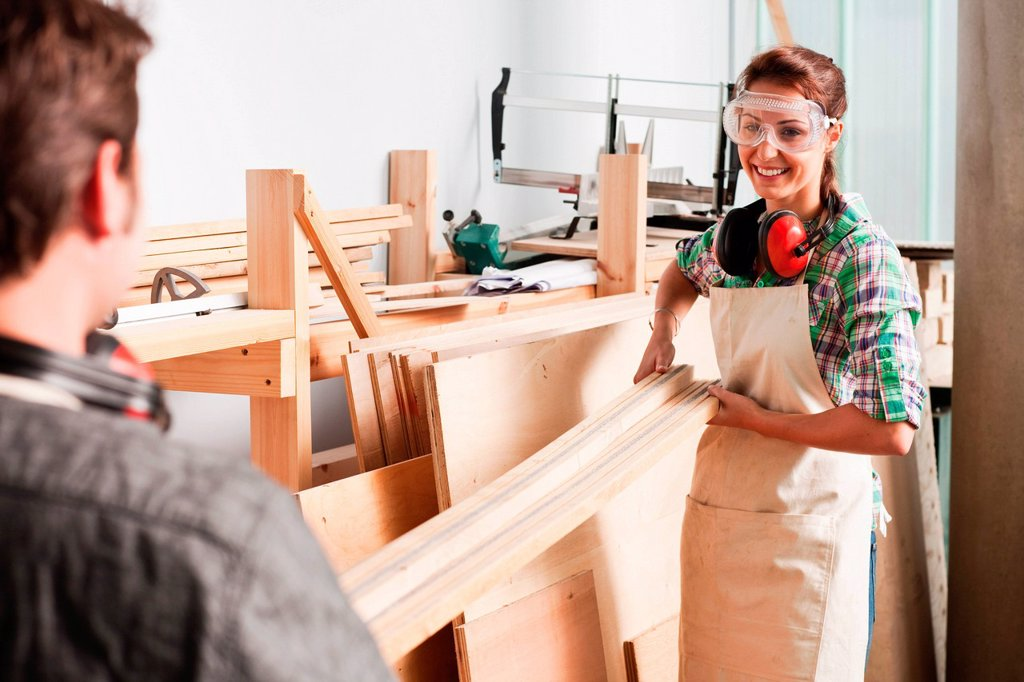 Carpenters carrying wood in workshop : Stock Photo
