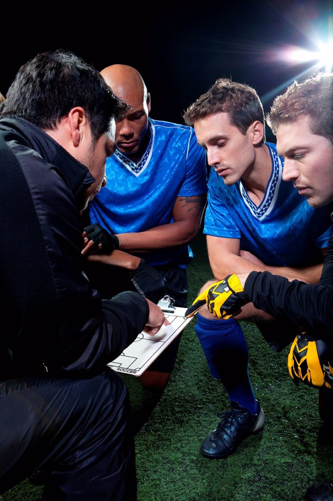 Stock Photo: 1439R-1141384 Soccer team planning game with coach
