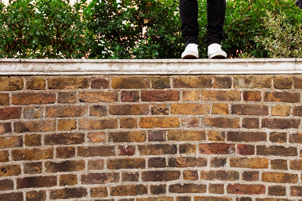 Stock Photo: 1439R-1141425 Woman in jeans standing on top of wall, low section