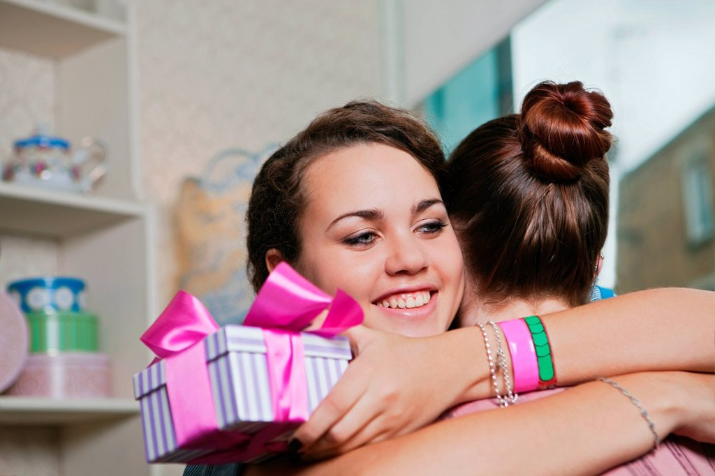 Stock Photo: 1439R-1141475 Young women holding birthday gift and embracing