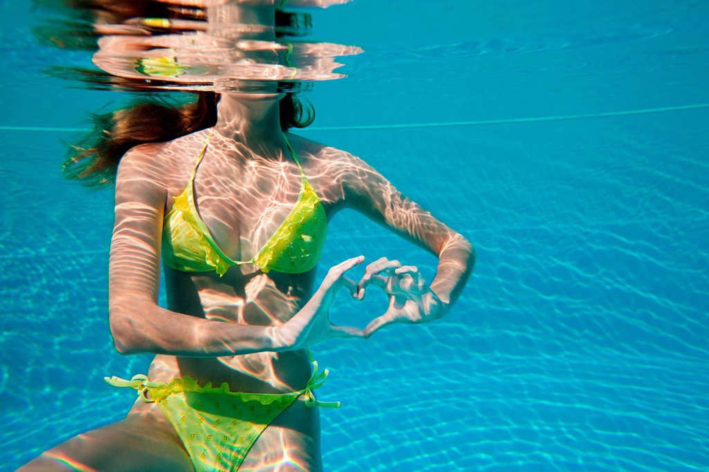 Young woman making heart shape with hands underwater in swimming pool : Stock Photo