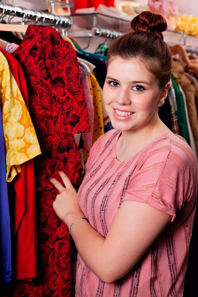 Stock Photo: 1439R-1141721 Young woman looking at dress in clothes shop, portrait