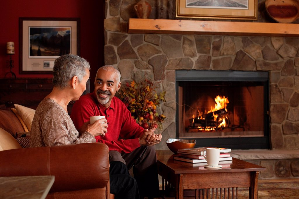 Stock Photo: 1439R-1141732 Mature couple sitting by fireplace
