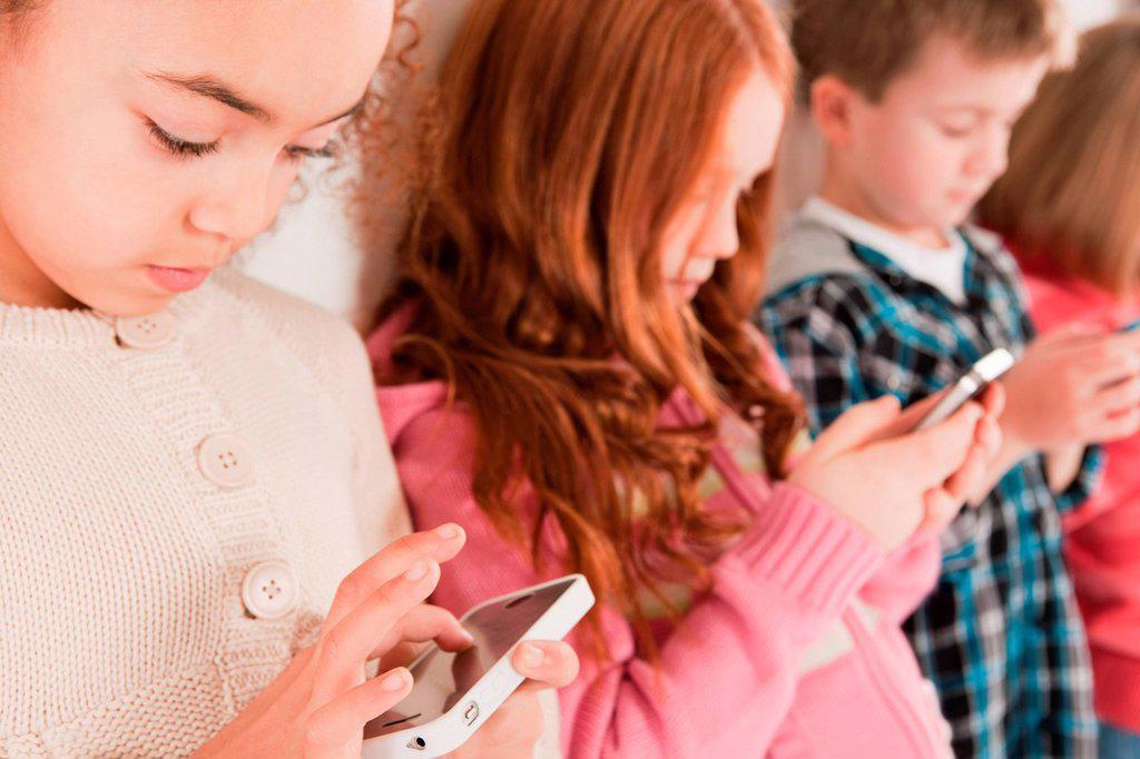 Children looking at smartphones : Stock Photo