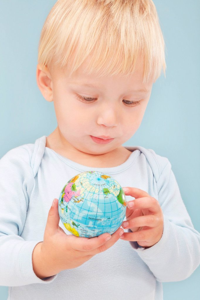 Stock Photo: 1439R-1141957 Little boy looking at little globe