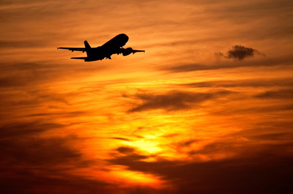 Airplane in in evening sky : Stock Photo