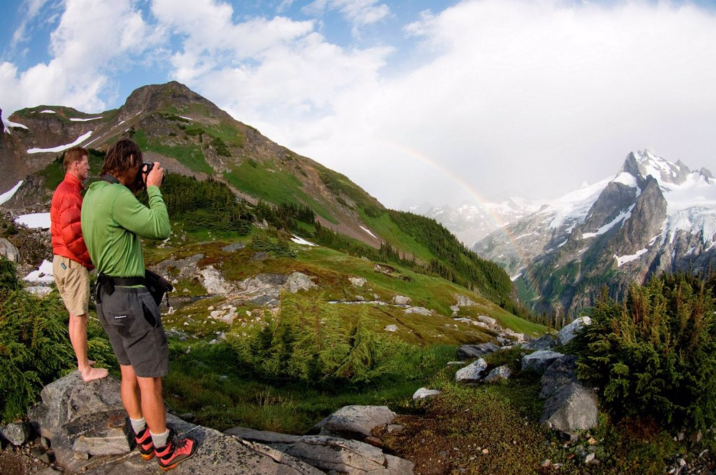 Stock Photo: 1439R-1142334 Photographing rainbow in mountains, White Rock Lakes, Ptarmigan Traverse, North Cascades, Washington, USA