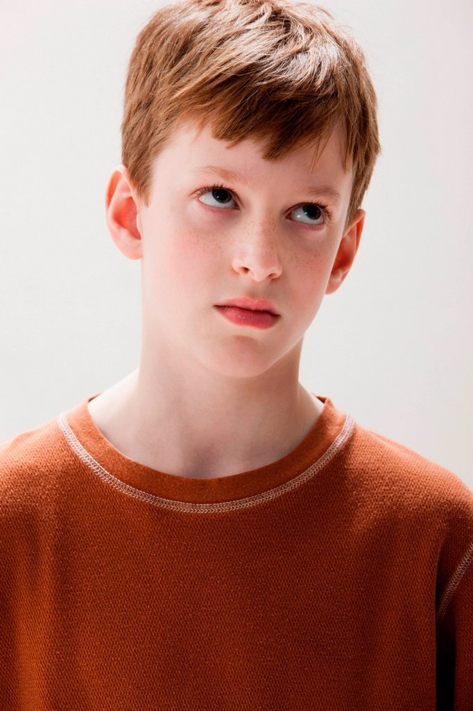 Stock Photo: 1439R-1142396 Boy in brown sweater rolling eyes, studio shot