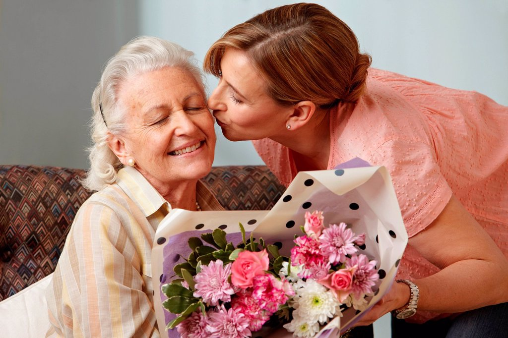 Stock Photo: 1439R-1142783 Daughter giving senior mother bouquet of flowers