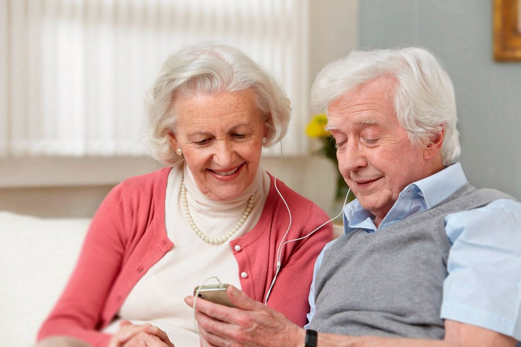 Stock Photo: 1439R-1142788 Senior couple listening to mp3 player