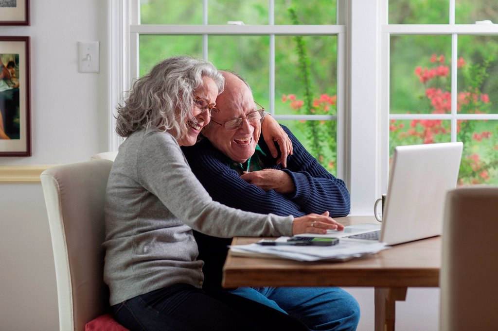 Stock Photo: 1439R-1143135 Senior couple using laptop at home, laughing