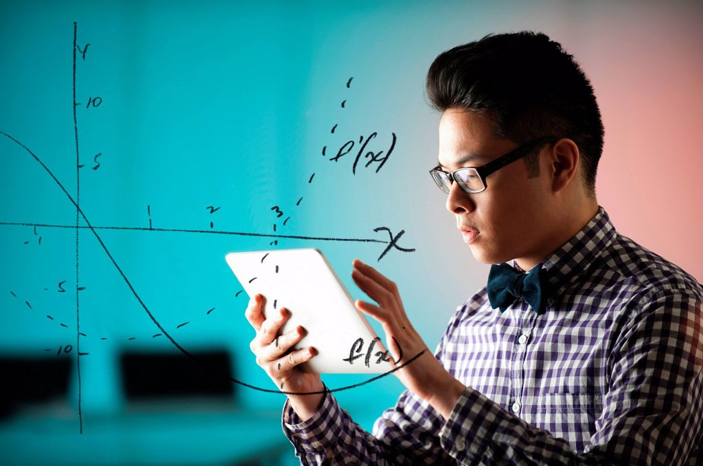Stock Photo: 1439R-1143328 Young man using digital tablet with diagram on window