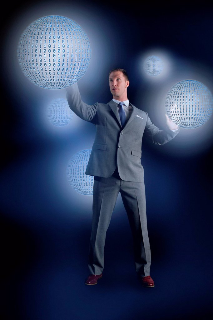 Stock Photo: 1439R-1143419 Businessman interacting with holographic binary globes