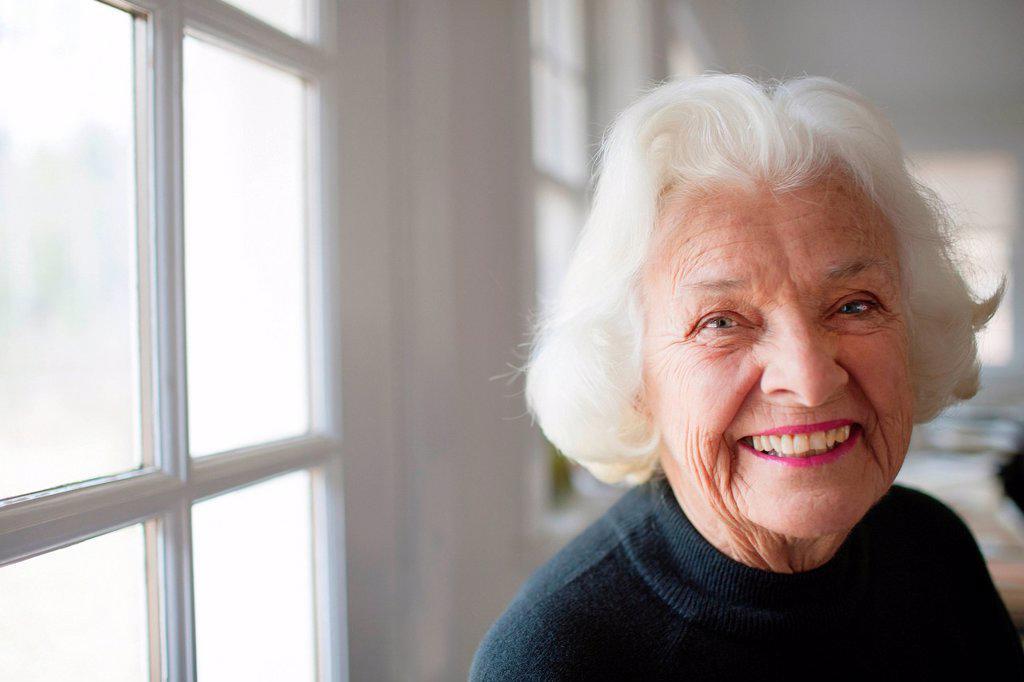Portrait of senior woman by window : Stock Photo