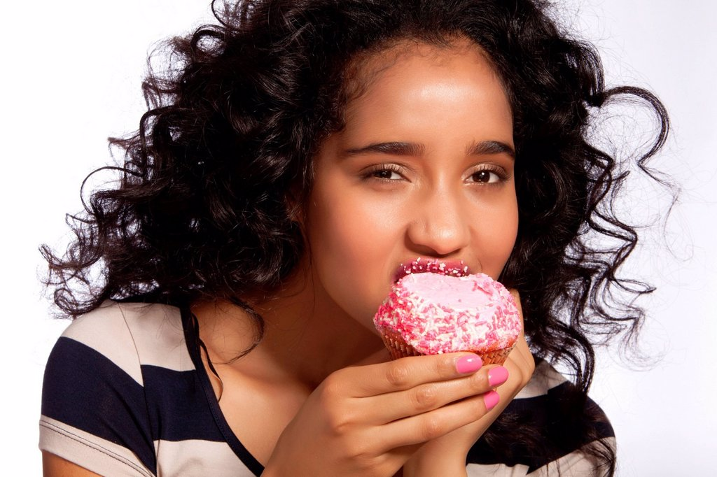 Young woman eating cupcake, studio shot : Stock Photo