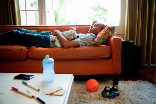 Man lying on sofa asleep with toys : Stock Photo