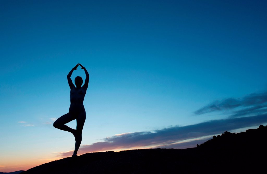Stock Photo: 1439R-1144000 Young woman in tree pose in desert, silhouette