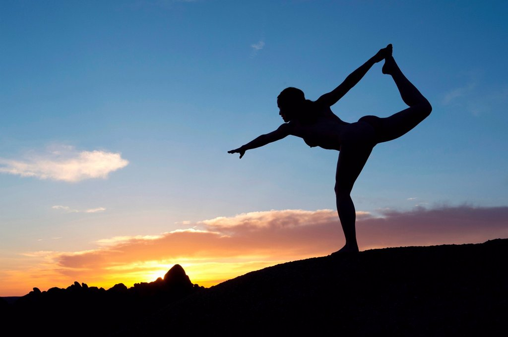 Young woman in dancer pose in desert, silhouette : Stock Photo