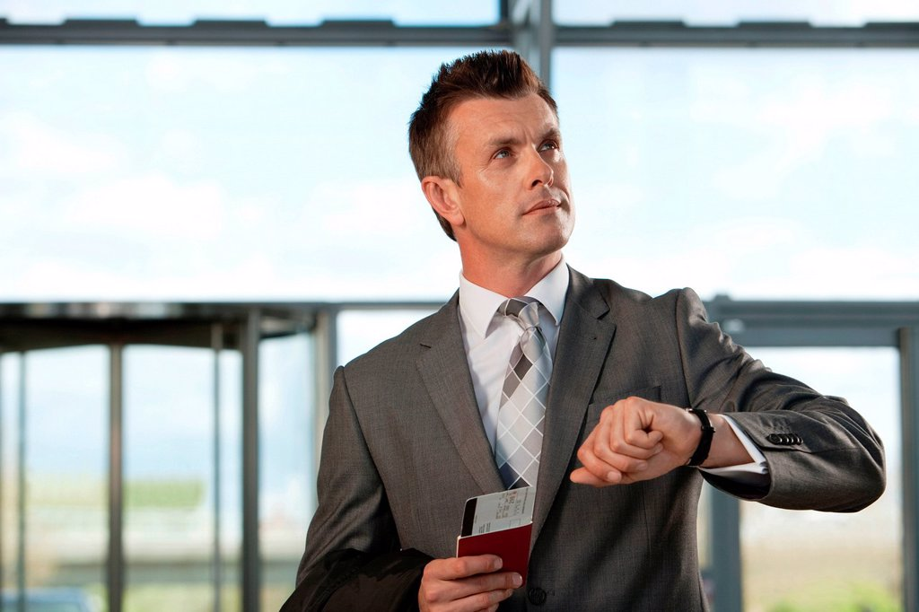 Businessman with airplane ticket and passport checking watch : Stock Photo