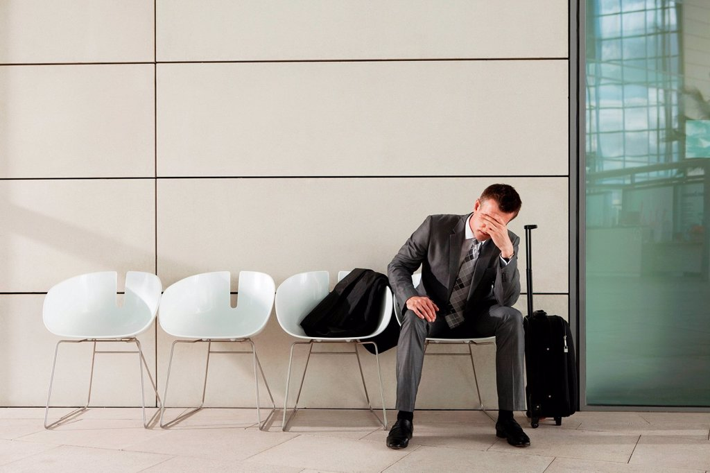 Stock Photo: 1439R-1144166 Businessman waiting with luggage and head in hands