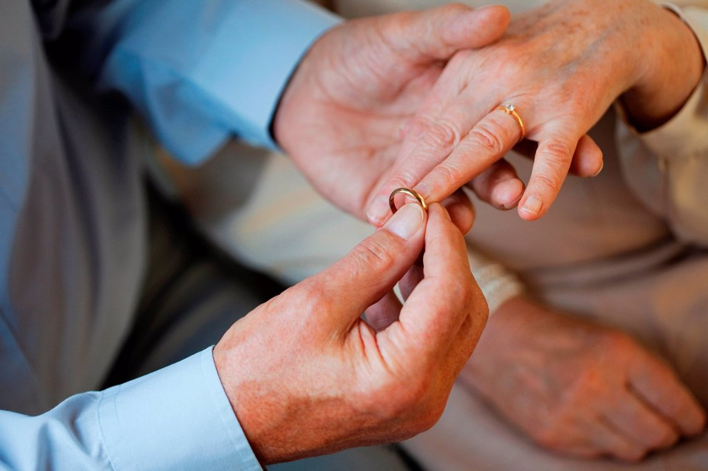 Stock Photo: 1439R-1144427 Senior man placing wedding ring on senior womans finger