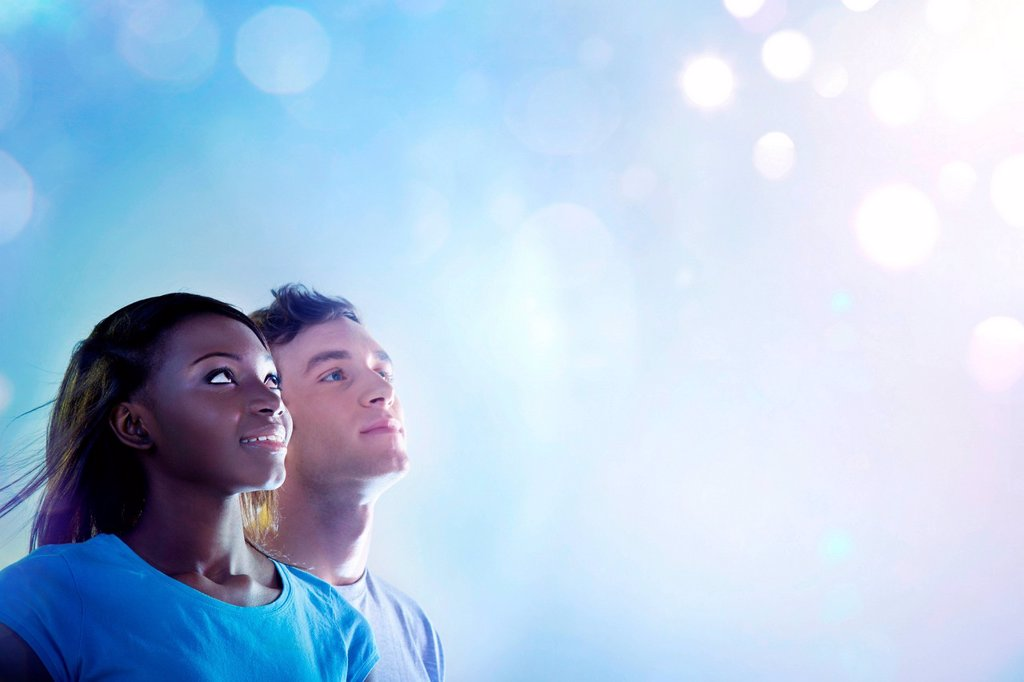 Young people looking up at light : Stock Photo