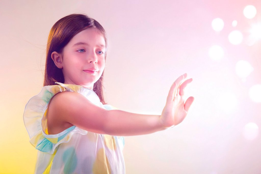 Stock Photo: 1439R-1144464 Girl reaching out to lights