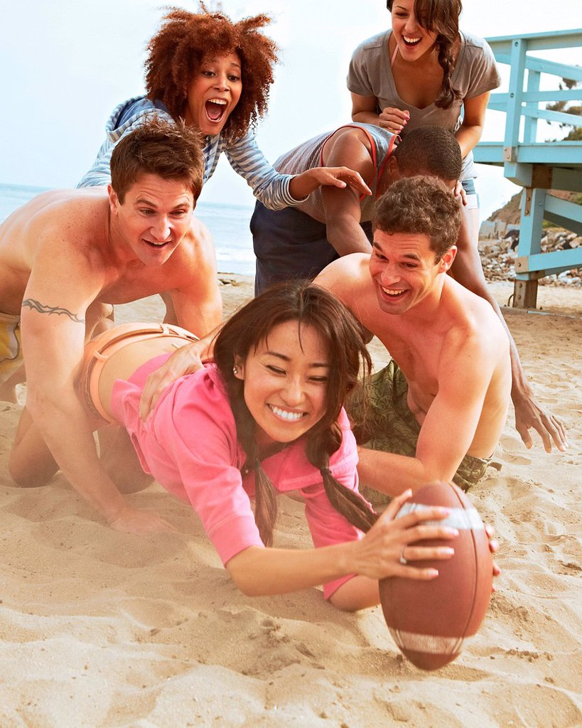 Stock Photo: 1439R-1144482 Friends on beach playing rugby