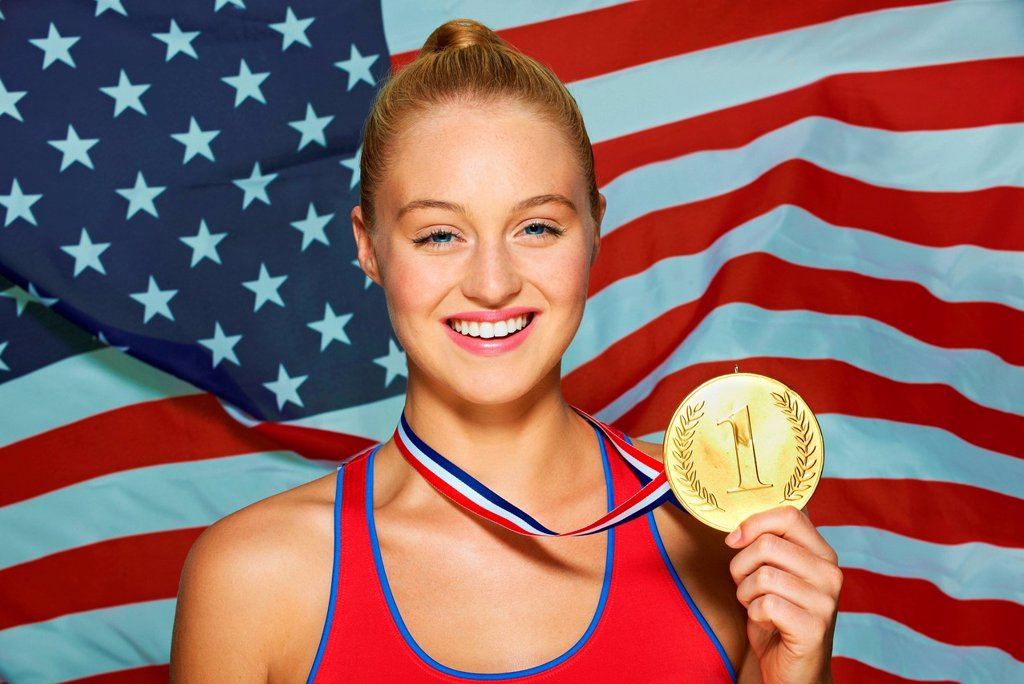 Young woman in front of USA flag with gold medal : Stock Photo