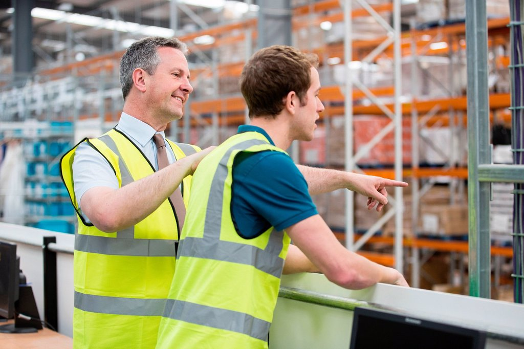 Stock Photo: 1439R-1144622 Two men in warehouse, one pointing
